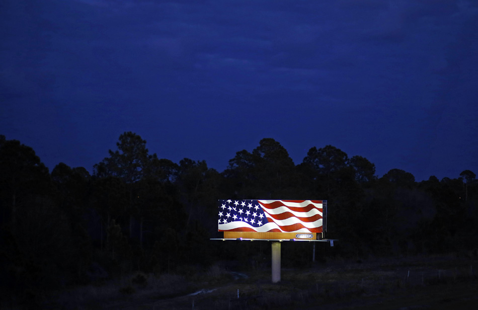 A billboard shows a depiction of the American flag alongside a highway at dusk in North Port, Fla., Sunday, Feb. 21, 2016. (AP Photo/Patrick Semansky)