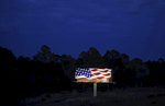 A billboard shows a depiction of the American flag alongside a highway at dusk in North Port, Fla.