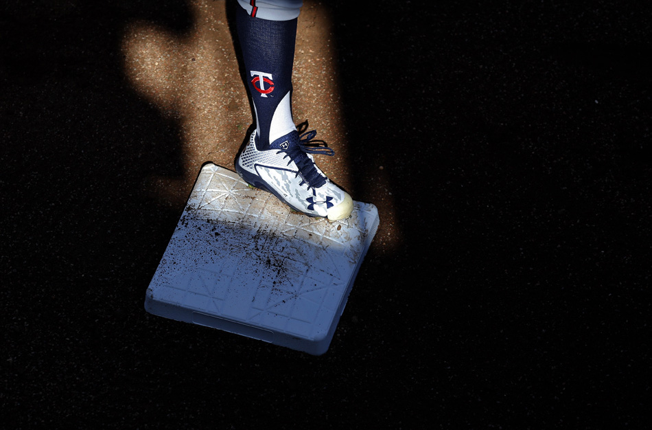 A patch of sunlight falls across first base as Minnesota Twins pitcher J.R. Graham runs a drill in Fort Myers, Fla.