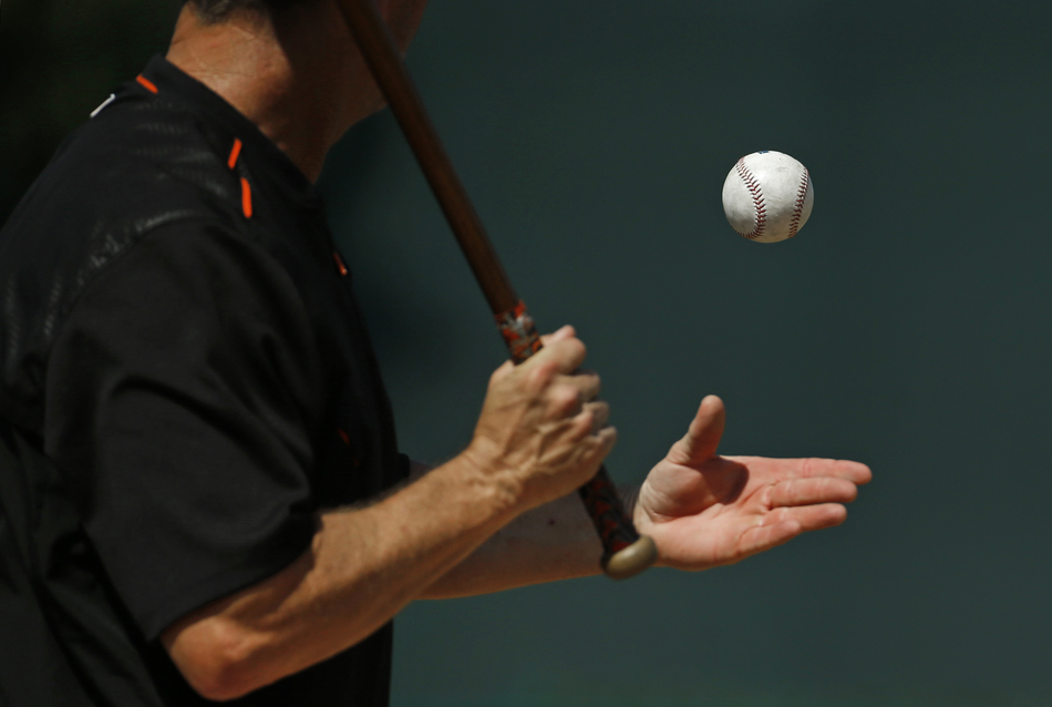 Baltimore Orioles third base coach Bobby Dickerson tosses a ball into the air before hitting it while running a drill in Sarasota, Fla.