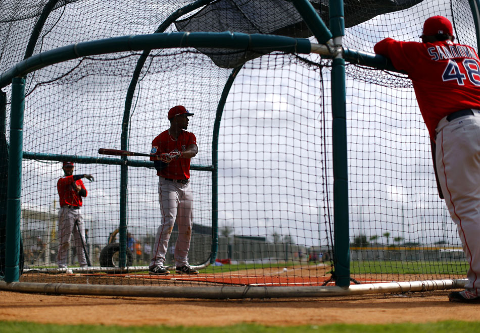 Boston Red Sox's Xander Bogaerts, center, takes batting practice as teammates Dustin Pedroia, back left, and Pablo Sandoval watch in Fort Myers, Fla.