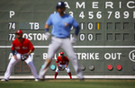 A scoreboard stands in left field behind members of the Boston Red Sox and Tampa Bay Rays during a game in Fort Myers, Fla.