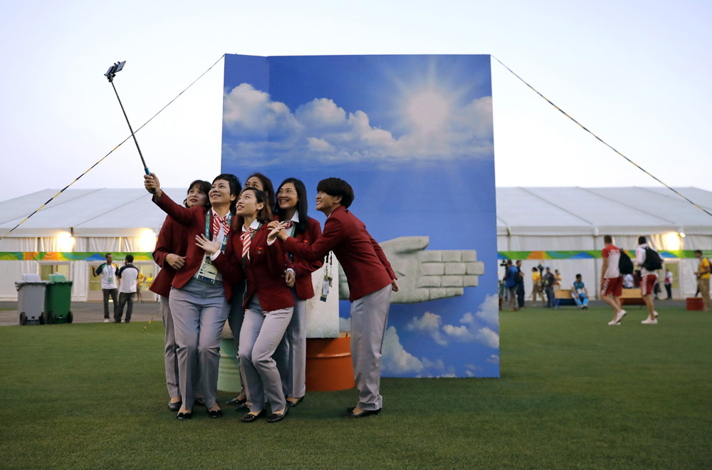 Members of the Vietnamese Olympic delegation pose for a selfie in front of a backdrop in athletes village in advance of the 2016 Olympic Games in Rio de Janeiro, Brazil.