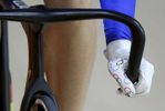 A member of the French men's track cycling team wears gloves emblazoned with Olympic rings as he rounds the track during a training session inside the Rio Olympic Velodrome during the 2016 Olympic Games.