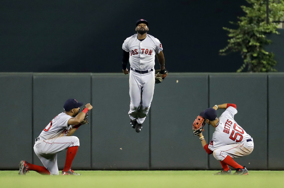 Boston Red Sox outfielders Chris Young, from left, Jackie Bradley Jr. and Mookie Betts celebrate after winning a baseball game against the Baltimore Orioles.