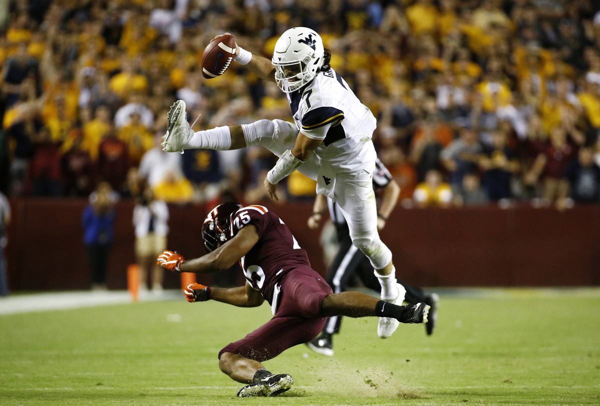 West Virginia quarterback Will Grier, top, leaps over Virginia Tech linebacker Anthony Shegog as he rushes for a first down during an NCAA college football game in Landover, Md.