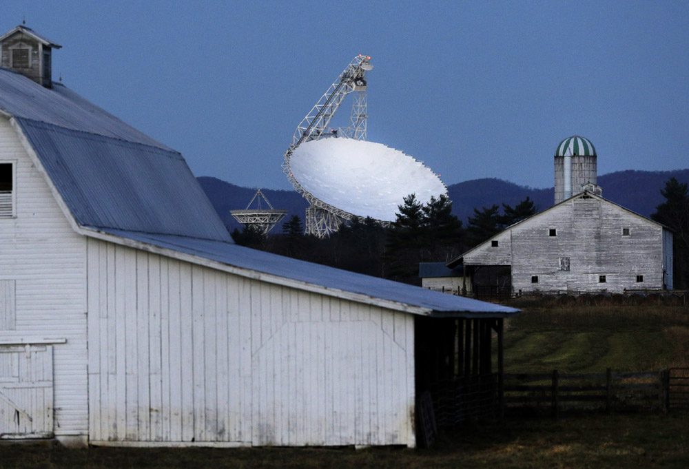 The Robert C. Byrd Green Bank Telescope towers over farmland as dusk falls in Green Bank, W.Va. Officials at the National Radio Astronomy Observatory chose the site for its remote location and mountainous surroundings, which help to keep distant radio waves outside of the quiet zone at bay, while interference inside the zone is restricted by state and federal laws. The quiet zone enables scientists to hear faint signals from outer space that would otherwise be easily obscured by man-made interference.