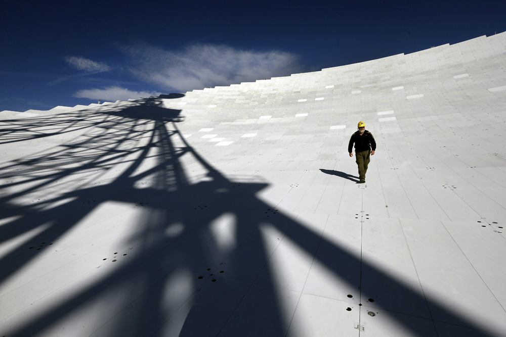 Michael Holstine, business manager at the National Radio Astronomy Observatory, walks on the 2.3 acre surface of the Robert C. Byrd Green Bank Telescope's dish. Scientists use the telescope to conduct a wide range of research, picking up faint signals that aid in the study of the origins and structure of the universe.