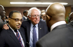Democratic presidential candidate, Sen. Bernie Sanders, I-Vt., center, puts his arm around Rev. Todd Yeary of Baltimore, as he speaks with African-American civic and religious leaders at the Freddie Gray Empowerment Center in Baltimore after taking a walking tour of Gray's neighborhood and participating in a roundtable discussion on issues affecting the African-American community.