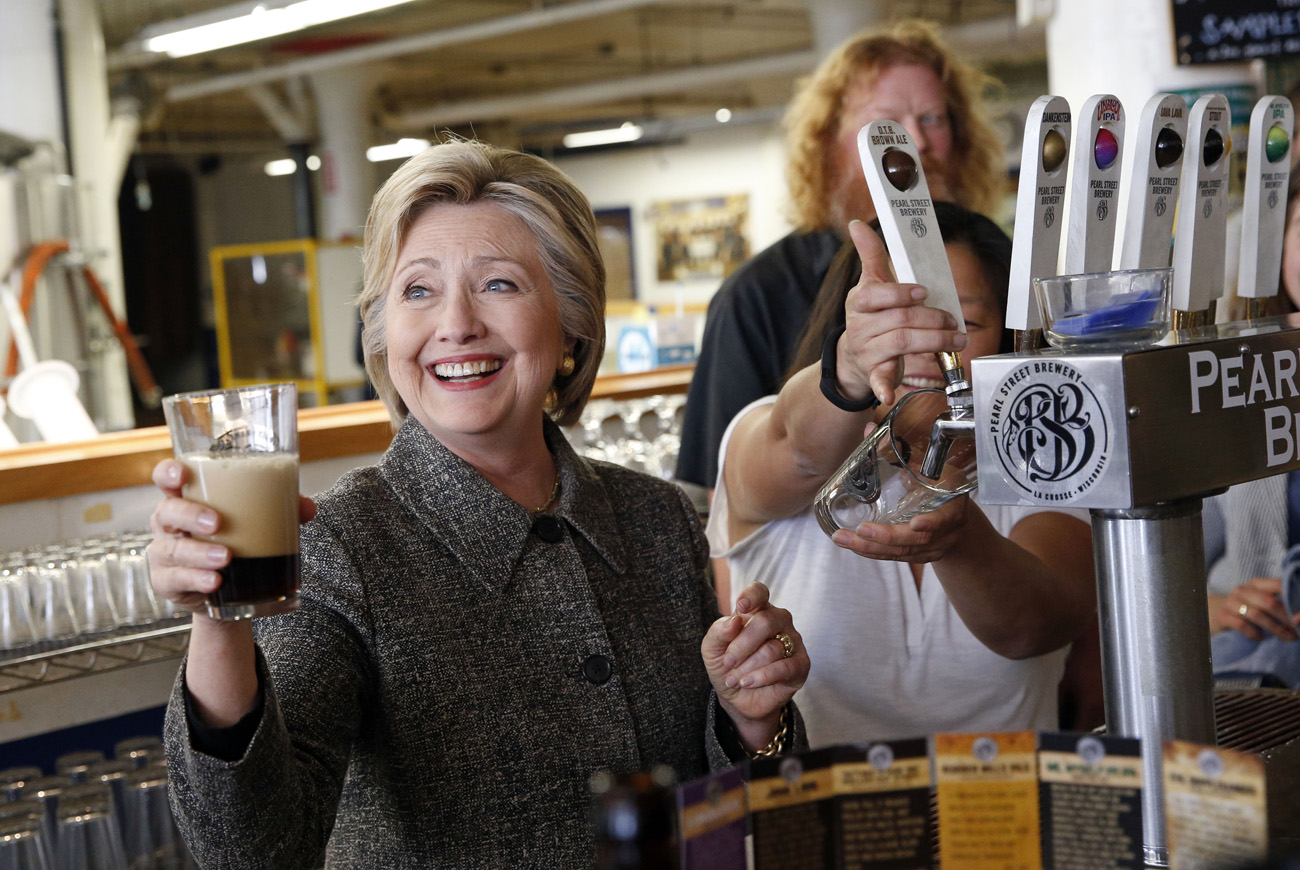 Democratic presidential candidate Hillary Clinton hoists a beer during a tour at Pearl Street Brewery in La Crosse, Wis.