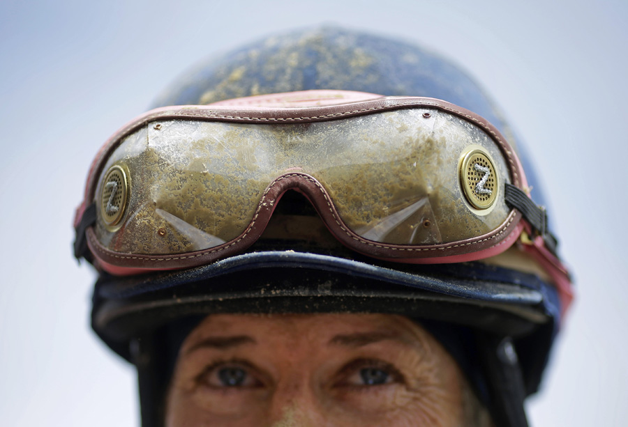Mud sticks to jockey Andrea Seefeldt Knight's goggles as she stands in the winner's circle after winning the Lady Legends for the Cure race at Pimlico Race Course in Baltimore.