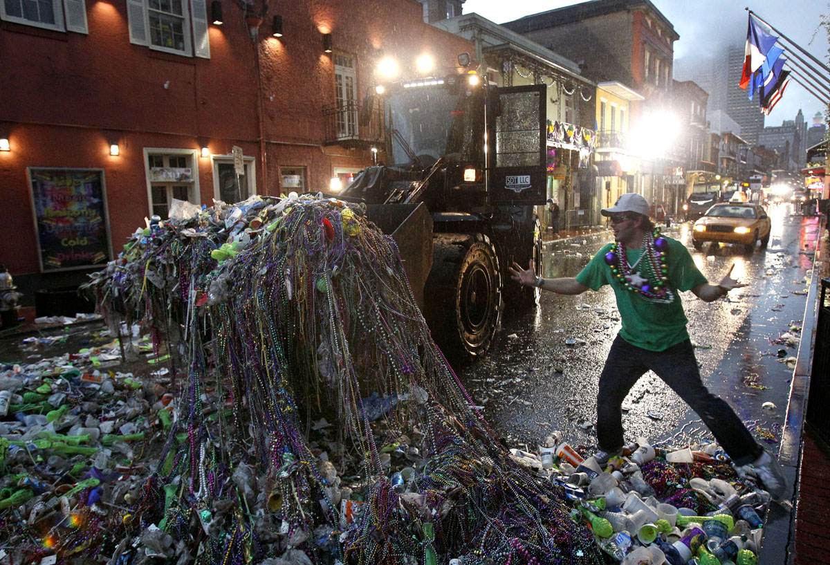 Mardi Gras reveler Mike Turpin, whose night still isn't over, reacts as a front loader collects beads and other debris left behind by revelers on Bourbon Street in the French Quarter of New Orleans early Ash Wednesday. Ash Wednesday marks the end of Mardi Gras festivities and the beginning of the Lenten season for Catholics.