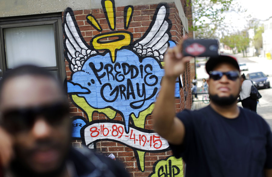 J.R. White, right, takes a selfie in front of a mural that was painted at the site of Freddie Gray's arrest as protesters prepare to march to Baltimore City Hall.