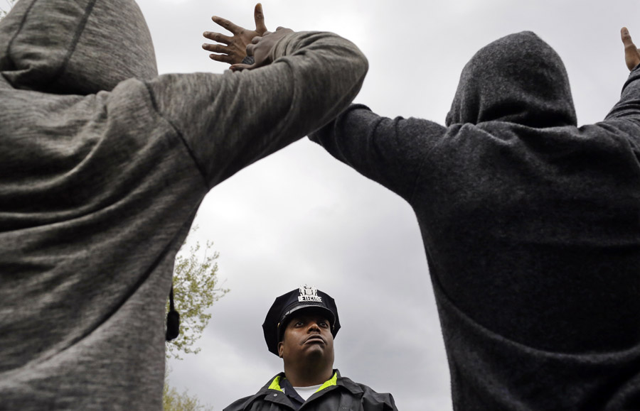 A member of the Baltimore Police Department stands guard outside of the department's Western District police station as men hold their hands up in protest during a march for Freddie Gray.