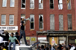 Blighted buildings stand behind a protester as he leads marchers in a chant from atop a vehicle.