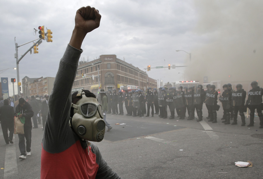 A demonstrator raises his fist as police stand in formation and a store burns during unrest following Freddie Gray's funeral.