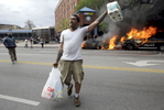 A man carries items from a store as police vehicles burn during unrest following Freddie Gray's funeral.