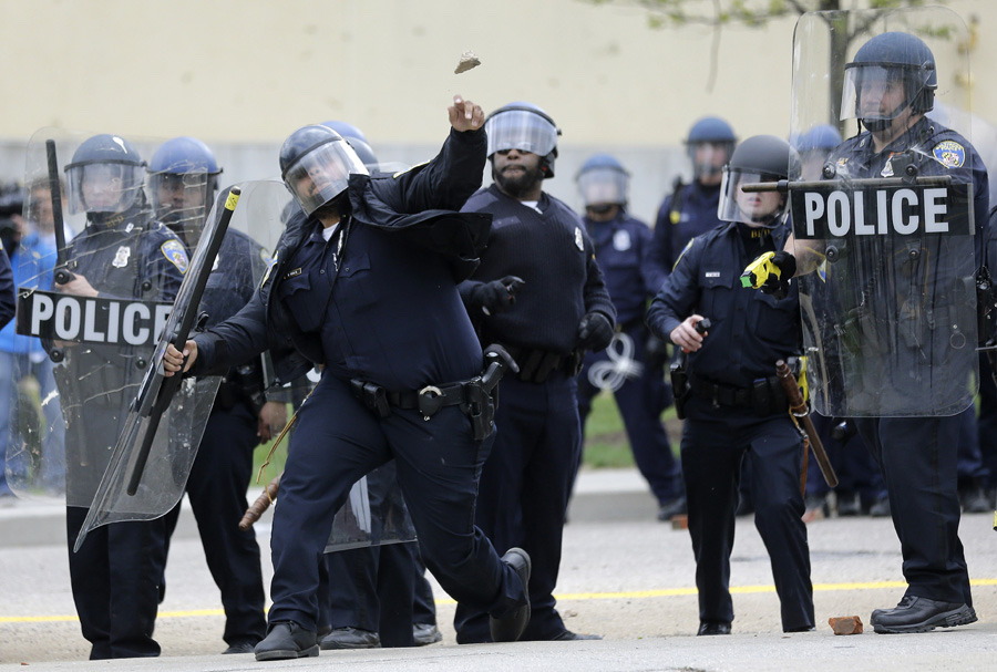 A police officer throws an object at protesters during unrest following Freddie Gray's funeral.