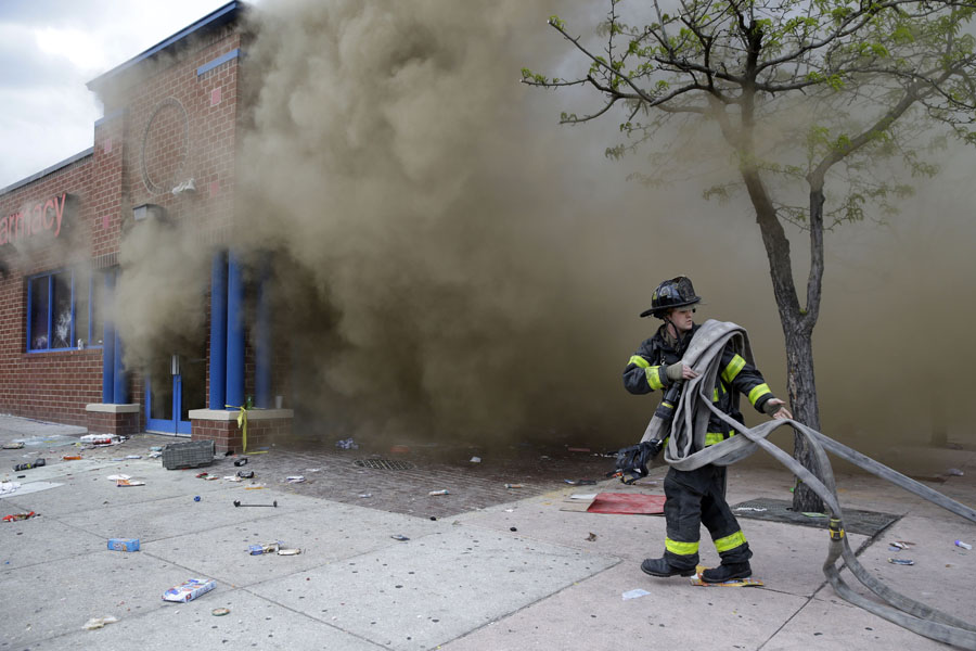 A firefighter pulls hoses toward a burning store during unrest following Freddie Gray's funeral.