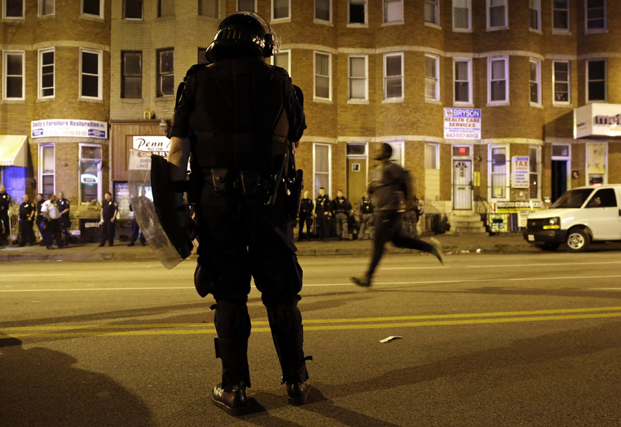 A law enforcement official watches a man run down North Avenue as curfew approaches.