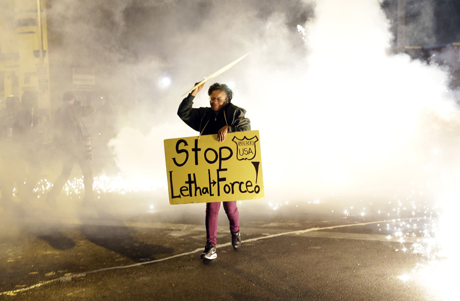 A woman runs for safety as police throw tear gas canisters while enforcing curfew.