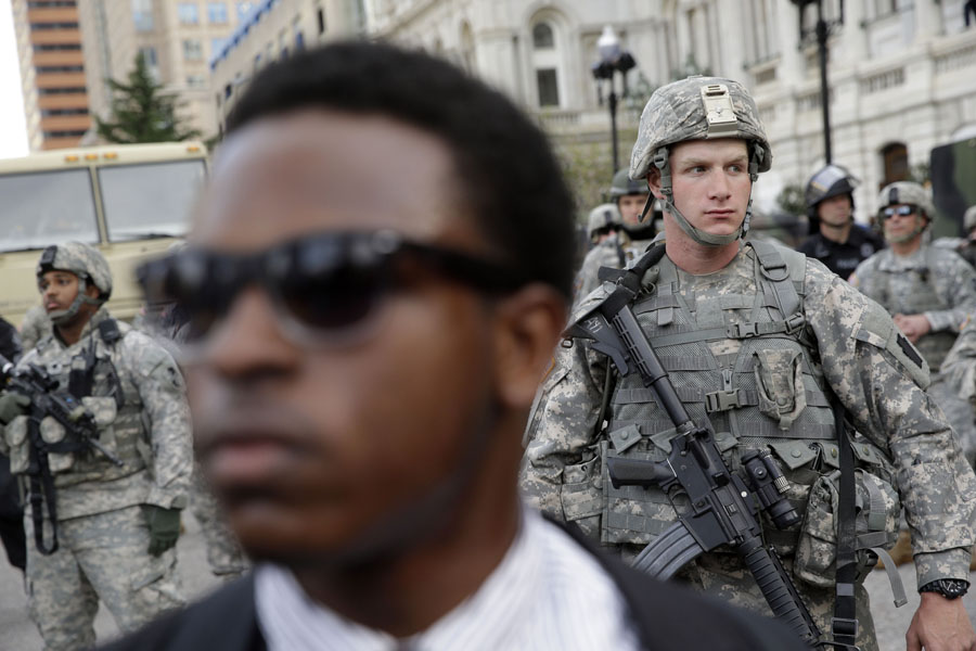 A member of the Maryland National Guard stands guard outside Baltimore City Hall as marchers protest the death of Freddie Gray.