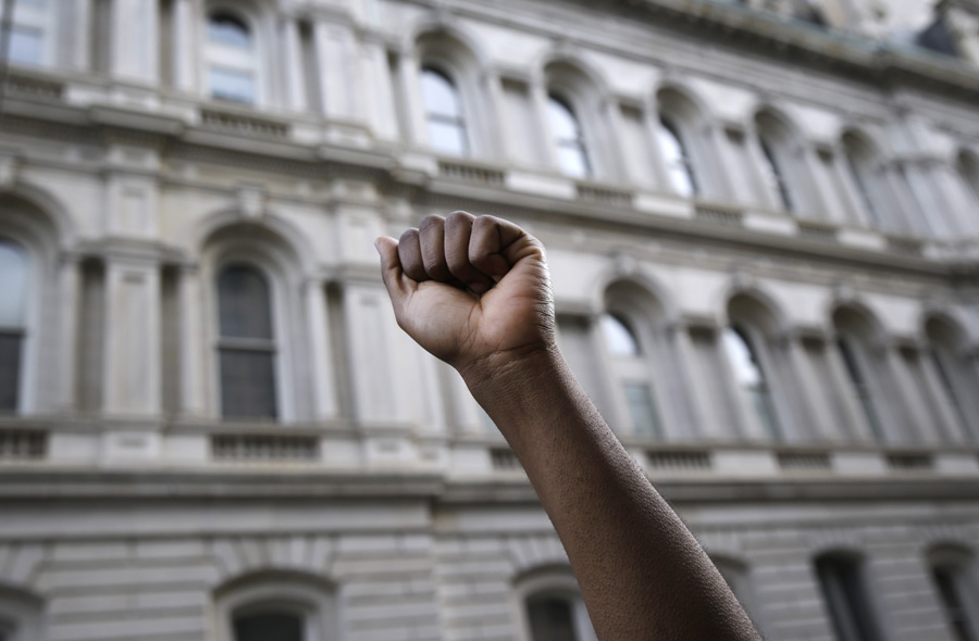 A protestor raises his fist outside of Baltimore City Hall as marchers protest Freddie Gray's death.