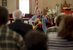 Rev. Rick Edmund plays guitar as he leads a service in the community of Tylerton on Smith Island, Md.