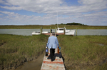 Rev. Rick Edmund walks to a waiting boat for a trip to a church service in the community of Tylerton on Smith Island, Md.