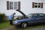 Rev. Rick Edmund tends to his disabled car between church services in the community of Ewell on Smith Island, Md.