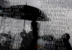 Visitors try to stay dry as rain falls on a monument that lists Hurricane Katrina victims who lived in St. Bernard Parish before a memorial service to commemorate the fifth anniversary of the storm in Shell Beach, La.