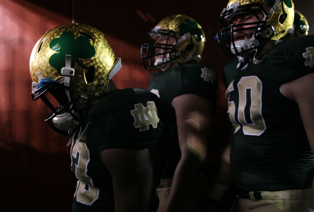Members of the Notre Dame football team walk out of a tunnel to the field before a game against Maryland in Landover, Md.