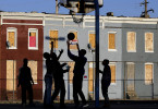 Children play basketball at a playground near blighted row houses in Baltimore. The U.S. Census Bureau estimates that 20 percent of American children are impoverished.