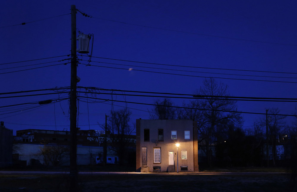 Two row houses, one boarded up, the other occupied, are surrounded by vacant lots at dusk in Baltimore. Baltimore has lost nearly a third of its population since it peaked in the 1950s, and today an estimated 16,000 buildings are vacant or abandoned.