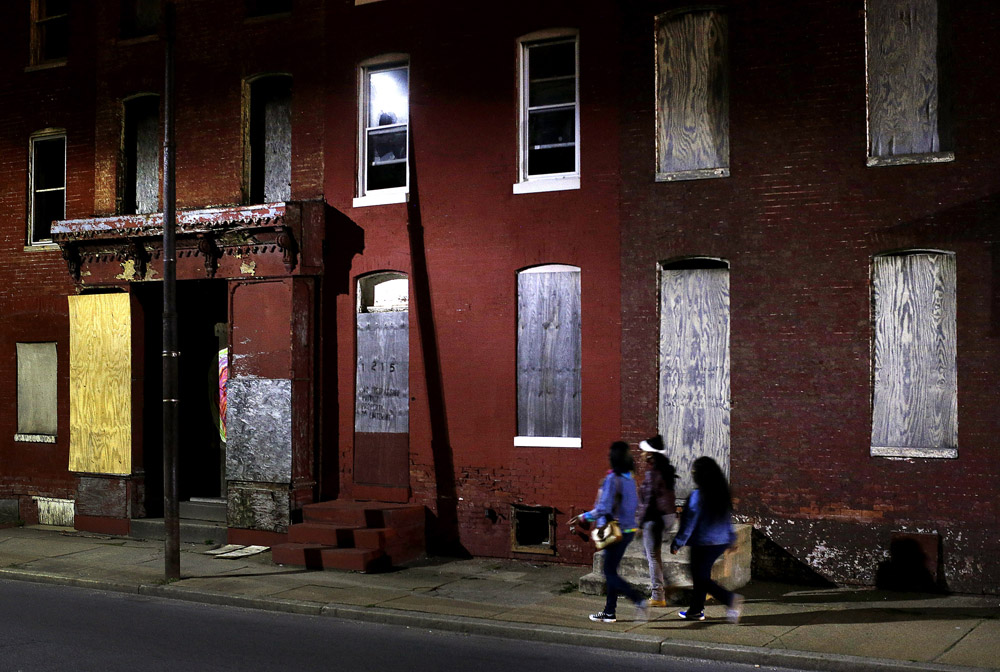 Women walk past blighted row houses in Baltimore.