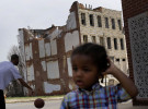 A boy plays across the street from a partially collapsed row house in Baltimore.