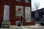 A boy shoots a basketball into a makeshift basket made from a milk crate and attached to a blighted row house in Baltimore.