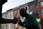 A pair of homeless men who gave their names as Earl, center, and Angelo eat ice cream cones across the street from a block of vacant row houses in Baltimore. A biennial census of Baltimore's homeless population counted over 4,000 homeless people in 2011. Some choose to seek shelter in the city's vacant buildings.