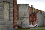 A man walks past blighted row houses and vacant lots in Baltimore.