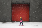 A woman walks as snow falls in Baltimore.