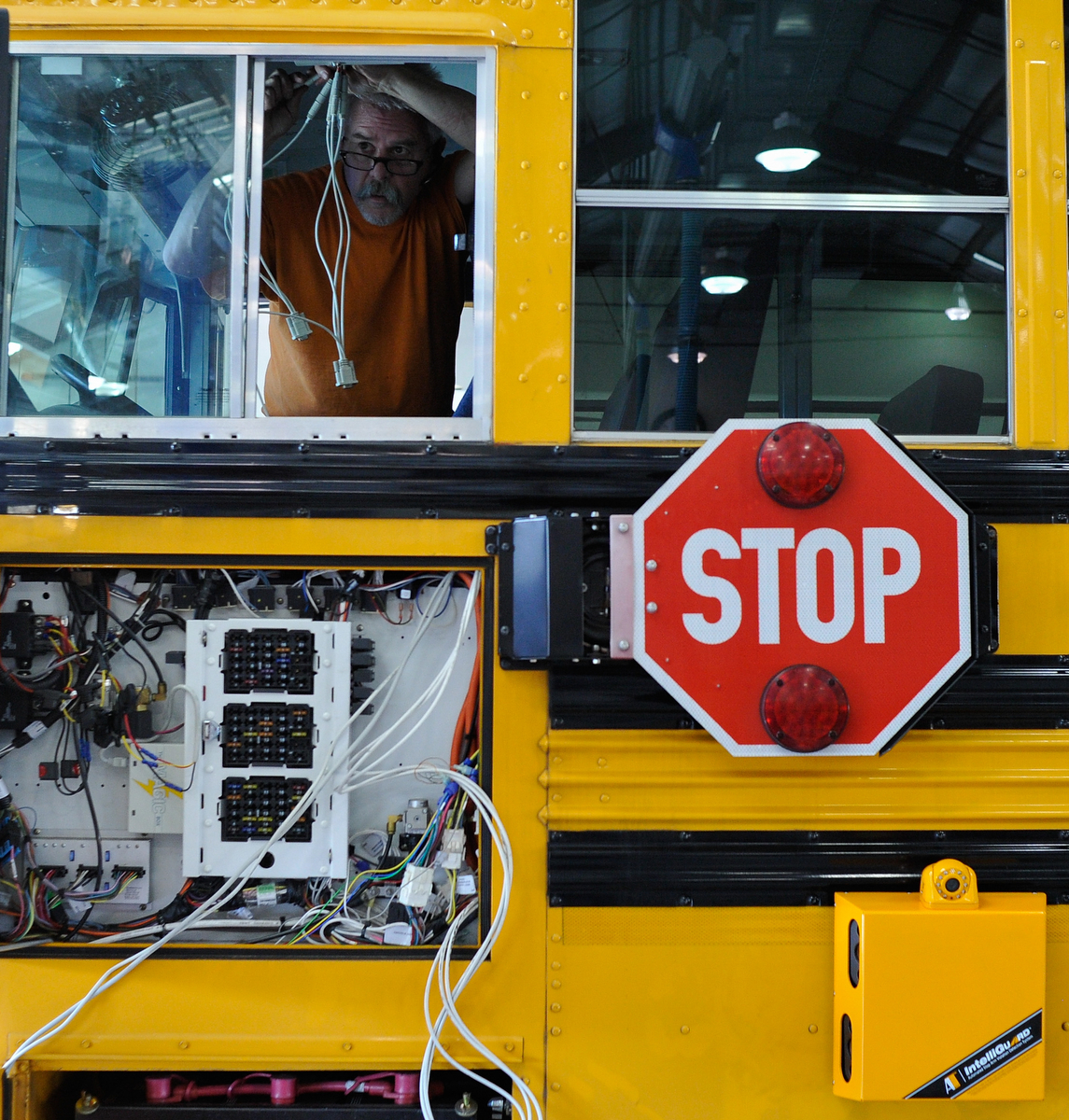 Ernie Stedman works on wiring a stop arm camera onto a Clarke County School Bus in Athens, Ga., Tuesday, Jan. 21, 2014. When the stop arm is activated, the camera photographs any automobile passing the school bus, resulting in a $300 traffic ticket. (AJ Reynolds/The Athens Banner-Herald)