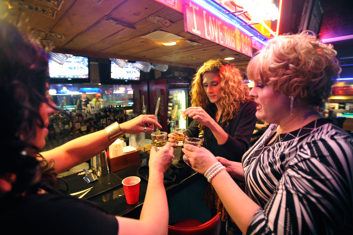 Lacie Bruce, from left, Diana Sativa and Sasha Stephens take a tequila shot inside Fuzion Bar & Grill before the show in Monroe, Ga., Friday, Jan. 10, 2014. (AJ Reynolds/Staff, @ajreynoldsphoto)