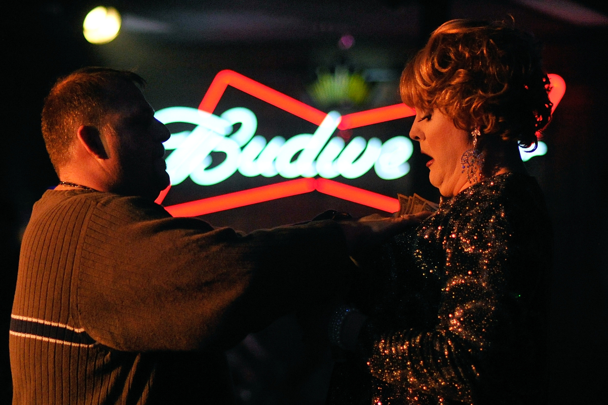 Show director Bryan Harris gives dollar bills to Sasha Stephens while she performs during Gender Fuzions Cabaret at Fuzions Bar & Grill in Monroe, Ga., Friday, Jan. 10, 2014. (AJ Reynolds/Staff, @ajreynoldsphoto)