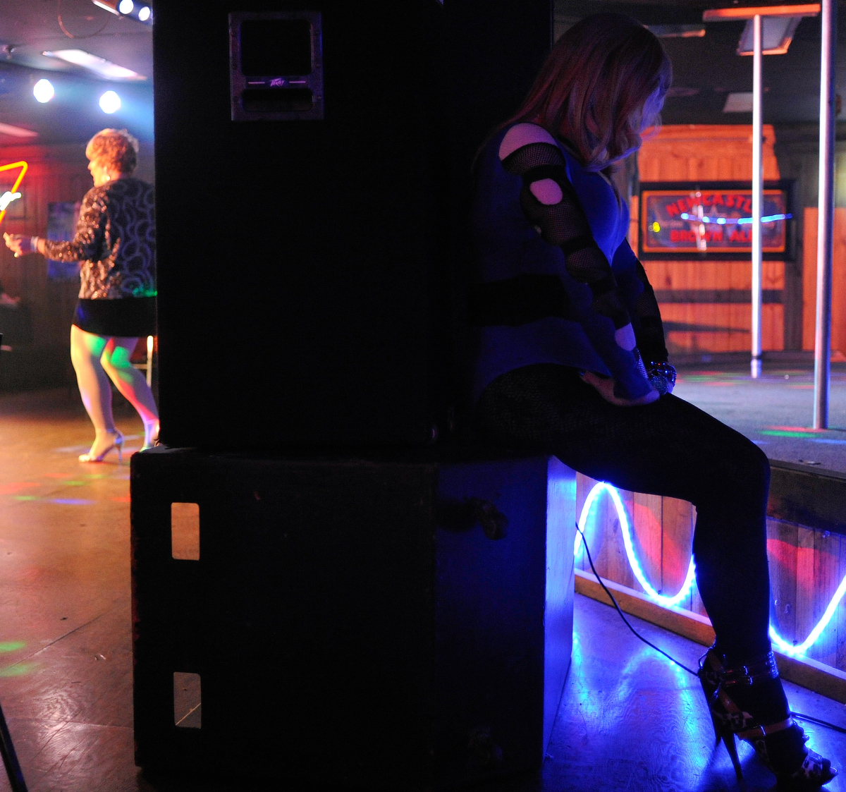Anita Richcock, right, waits behind a set of speakers while Sasha Stephens performs during the Gender Fuzions Cabaret at Fuzions Bar in Monroe, Ga., Friday, Jan. 10, 2014. (AJ Reynolds/Staff, @ajreynoldsphoto)