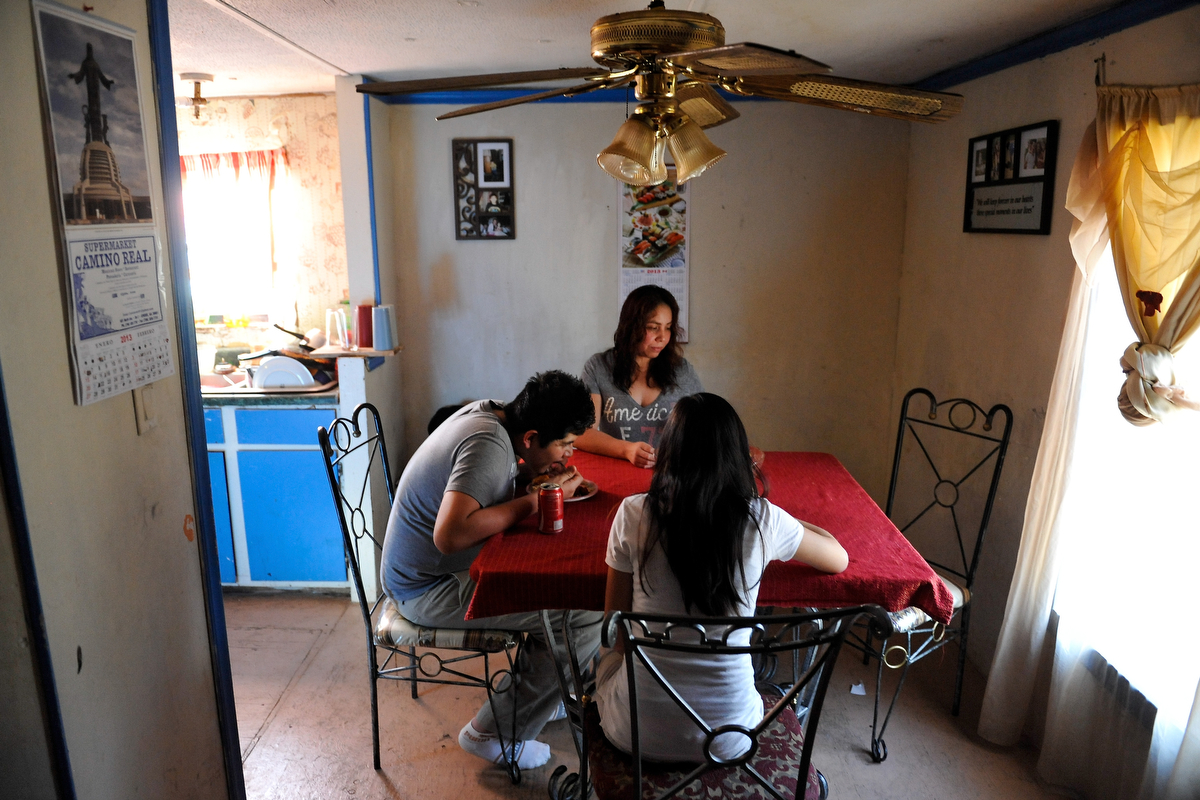 Sandra Juarez sits while two of her children eat {quote}arroz con pollo{quote} after school in Athens, Ga., Wednesday, Feb. 6, 2013. Juarez has raised her four children on her own since their father, Jose Arreola, was deported in June 2011. (AJ Reynolds/The Athens Banner-Herald)