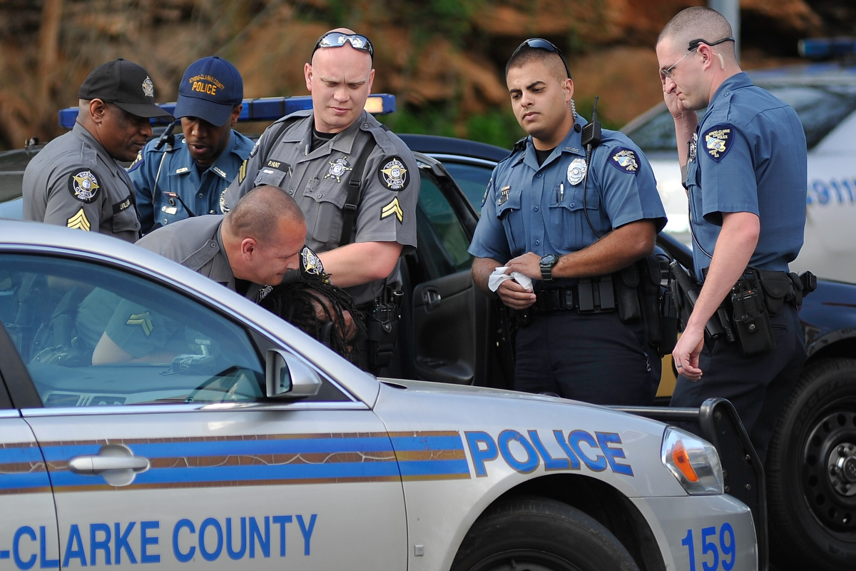 Athens-Clarke County Police and Sheriffs officers detain Tyrone Reese at the Quick Pantry at the intersection of North Avenue and Dr. Martin Luther King Parkway on Tuesday, March 24, 2015, in Athens, Ga. Reese ran from officers who approached Reese to enforce his ban from the Quick Pantry. (AJ Reynolds/Staff, @ajreynoldsphoto)