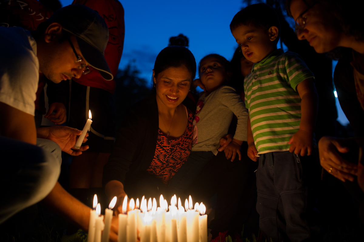 Jyotsna Ghimire, center, holds her daughter Aditi Ghimire while placing their candles with others during a candlelight vigil remembering and honoring the victims of the Nepal Earthquake on Friday, May 1, 2015, in Athens, Ga. (AJ Reynolds/Staff)