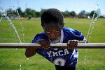 Shamir Stokes, 8, takes a drink during a water break at the YMCA 2015 Spring Football Clinic on Saturday, May 2, 2015, in Athens, Ga. (AJ Reynolds/Staff)
