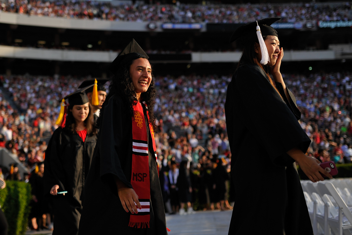 A graduate wipes a tear from her face while processing into Sanford Stadium for the University of Georgia Undergraduate Commencement on Friday, May 8, 2015, in Athens, Ga. (AJ Reynolds/Staff, @ajreynoldsphoto)