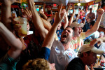Morgan Beaty, center, and other fans cheer after the United States first goal while watching the United States World Cup match against Ghana at the Royal Peasant on Monday, June 16, 2014, in Athens, Ga. (AP Photo/Athens Banner-Herald, AJ Reynolds)
